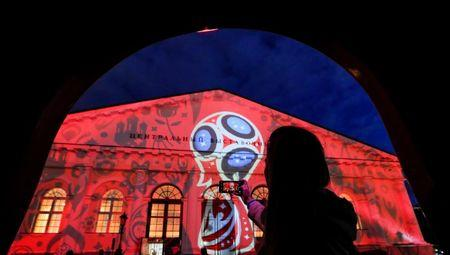 A woman takes pictures of Moscow's Manezh building during a preview of laser show devoted to 2018 FIFA World Cup in Moscow
