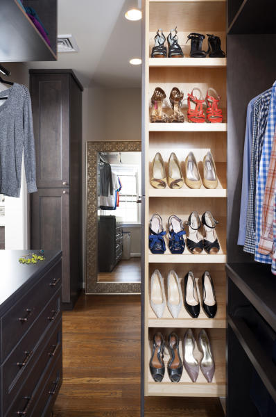 This photo provided by Case Design shows a closet designed by Elena Eskandari, an interior designer specialist at Case Design. A retractable shoe storage area in this closet keeps shoes organized and easily visible for the homeowner. As you plan out a walk-in closet, consider the size of the items you'll be hanging. (Stacy Zarin Goldberg/Case Design via AP)