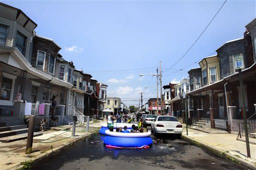 Residents block cars and set up a pool on the street to swim on Wednesday, June 20, 2012, in Philadelphia. Temperatures climbed toward the high 90s along the Eastern Seaboard as an unusually early hot spell heralded the official start of summer. (AP Photo/Brynn Anderson)