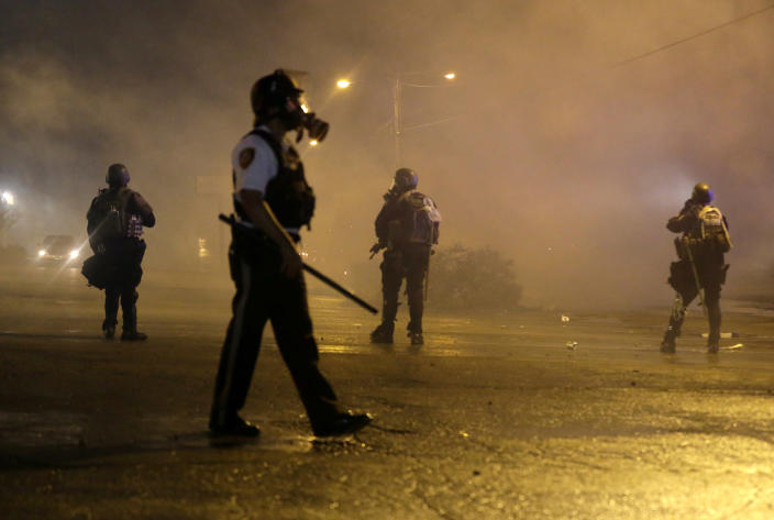 FILE - In this Aug. 17, 2014 file photo, law enforcement officers watch as tear gas is fired to disperse a crowd protesting the shooting of 18-year-old Michael Brown in Ferguson, Mo. As police departments in Missouri and across the country push to outfit officers with body cameras as a means to increase transparency following Brown's fatal shooting, two Republican state legislators are trying to restrict public access to those videos. (AP Photo/Charlie Riedel, File)