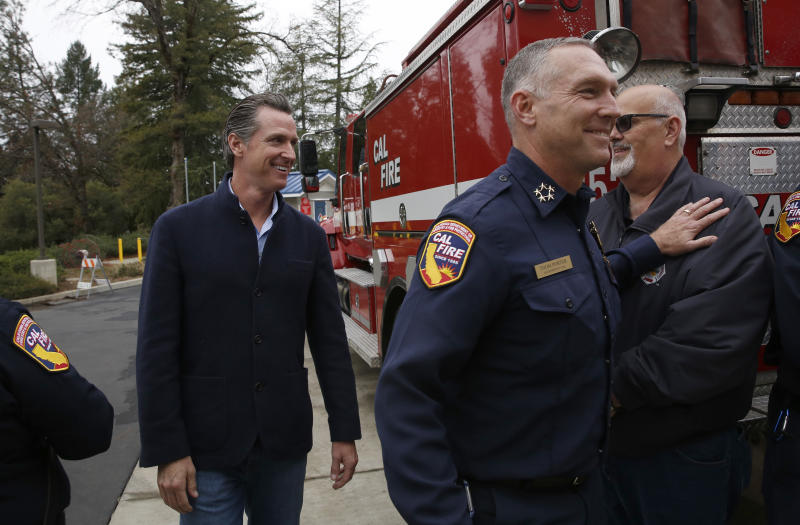Gov. Gavin Newsom, left, is escorted by Thom Porter, right, to the California Department of Forestry and Fire Protection CalFire Colfax Station Tuesday, Jan. 8, 2019, in Colfax, Calif. On his first full day as governor, Newsom announced executive actions to improve the state's response to wildfires and other emergencies. Earlier Newsom appointed Porter, to head the state's firefighting agency. (AP Photo/Rich Pedroncelli)