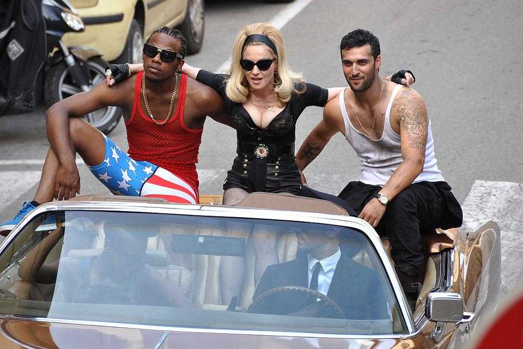"Across the Atlantic in Florence, Italy, Madonna cozied up with a couple of young hunks in the back of a convertible while shooting a video for her new tune ""Turn Up The Radio"" on Tuesday. We're sure most other 53-year-old women would be envious! (6/19/2012)"