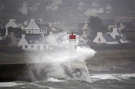 Waves crash over the lighthouse at Audierne in Brittany as an Atlantic storm hits western France, December 23, 2013. REUTERS/Mal Langsdon