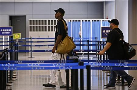 Former basketball star Dennis Rodman walks towards China's Frontier Inspection point as he transits to Pyongyang from Beijing Capital International Airport