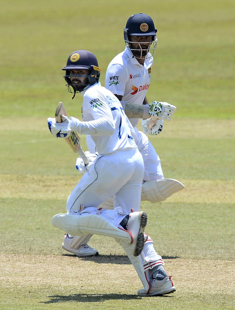 Sri Lankan batsman Dhanajaya De Silva, left, and Dimuth Karunaratna run between wickets during the fourth day of the first test cricket match between Sri Lanka and Bangladesh in Pallekele, Sri Lanka, Saturday, April 24, 2021.( AP Photo/Sameera Peiris)