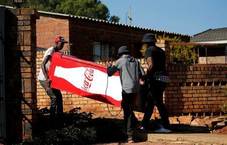 Locals carry a Cocacola branded refrigerator they looted at a nearby shop during protests in Atteridgeville, a township located to the west of Pretoria, South Africa June 21, 2016. REUTERS/Siphiwe Sibeko
