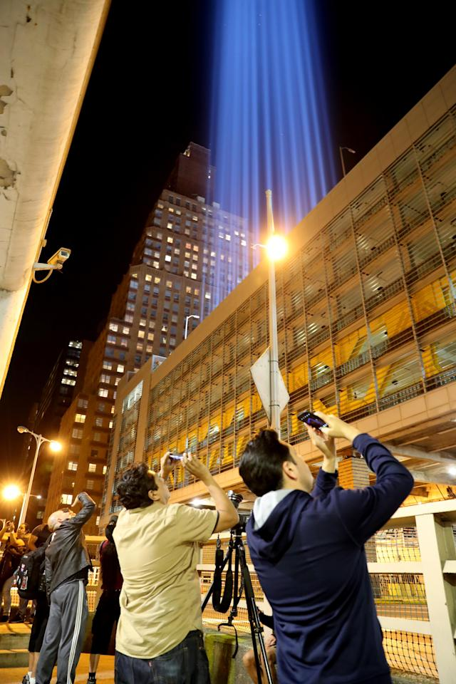 <p>People on the street take photos with their mobile device from the rooftop of where the beams of lights are projected on Sept. 11, 2017. (Gordon Donovan/Yahoo News) </p>