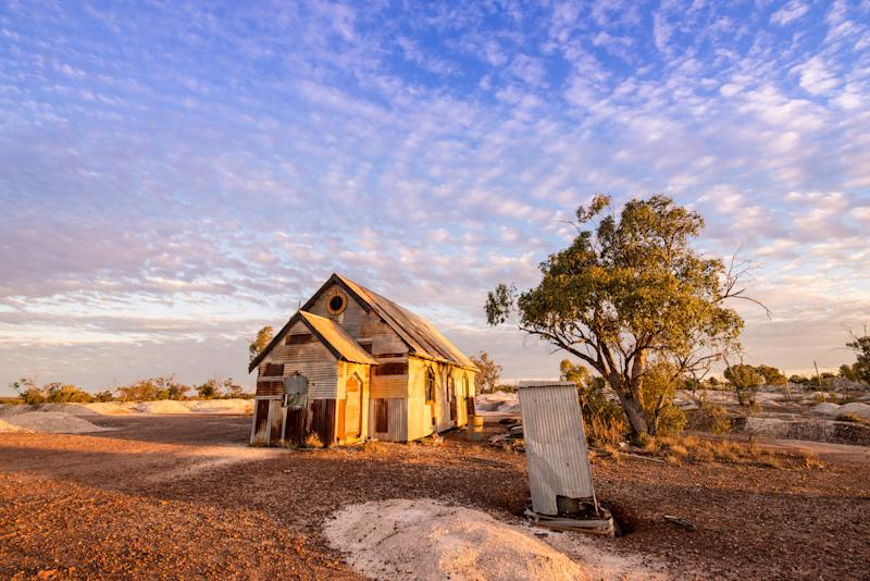 Rusty old corrugated iron church below mackerel sky of glowing cirrocumulus clouds at dusk. The church, once part of a film set, sits deserted on the dry opal fields at Lightning Ridge, a small town in northern New South Wales, Australia. A small corrugated metal dunny (toilet) stands at right.