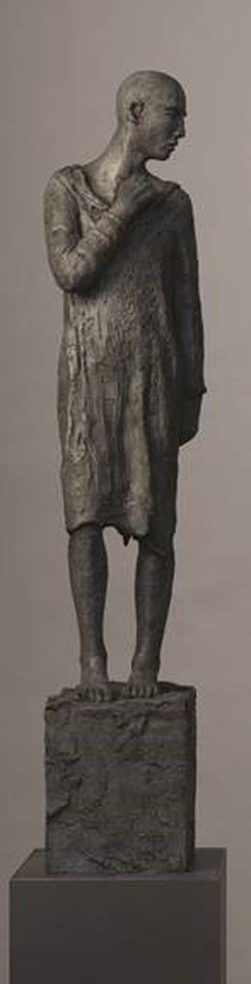 A bronze, androgynous statue looking to its left.
