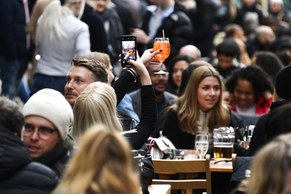 FILE - In this Monday, April 12, 2021 file photo, a woman takes a photo on her phone of her drink in Soho, London, as some of England's coronavirus lockdown restrictions were eased by the government. Thanks to an efficient vaccine roll out program and high uptake rates, Britain is finally saying goodbye to months of tough lockdown restrictions. From Monday May 17, 2021, all restaurants and bars can fully reopen, as can hotels, cinemas, theatres and museums, and for the first time since March 2020, Britons can hug friends and family and meet up inside other people's houses. (AP Photo/Alberto Pezzali, File)