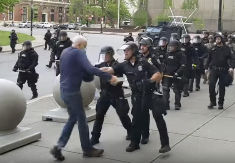 """In this image from video provided by WBFO, a Buffalo police officer appears to shove a man who walked up to police Thursday, June 4, 2020, in Buffalo, N.Y. Video from WBFO shows the man appearing to hit his head on the pavement, with blood leaking out as officers walk past to clear Niagara Square. Buffalo police initially said in a statement that a person """"was injured when he tripped & fell,"""" WIVB-TV reported, but Capt. Jeff Rinaldo later told the TV station that an internal affairs investigation was opened. Police Commissioner Byron Lockwood suspended two officers late Thursday, the mayor's statement said. (Mike Desmond/WBFO via AP)"""