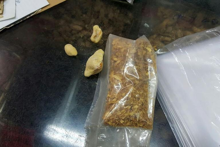 Deep fried pangolin scales next to a bag containing shredded pangolin scales at a traditional Chinese medicine store in Hong Kong
