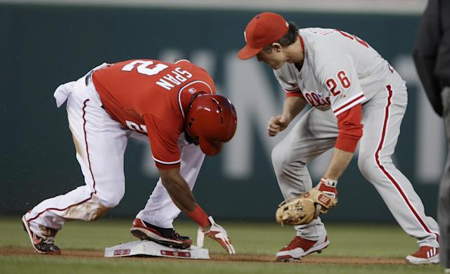 Washington Nationals' Denard Span, left, reaches second before Philadelphia Phillies Chase Utley, right, can apply the tag, on a stolen base during the first inning of a baseball game at Nationals Park, Saturday, Sept. 14, 2013, in Washington. (AP Photo/Pablo Martinez Monsivais)