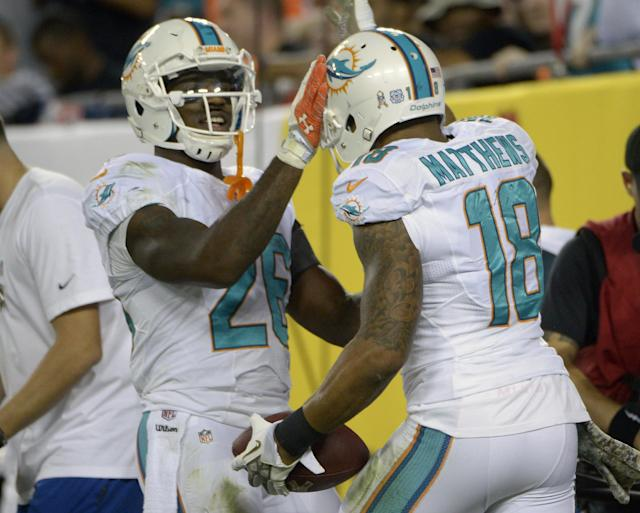 Miami Dolphins running back Lamar Miller, left, celebrates a touchdown by wide receiver Rishard Matthews (18) against the Tampa Bay Buccaneers during the first half of an NFL football game in Tampa, Fla., Monday, Nov. 11, 2013.(AP Photo/Phelan M. Ebenhack)
