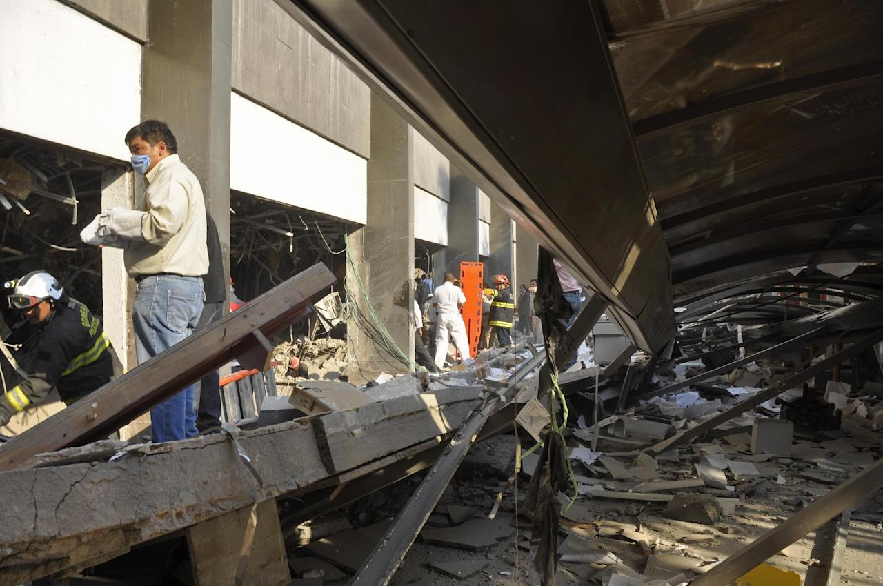 Firefighters belonging to the Tacubaya sector and workers dig for survivors after an explosion at a building adjacent to the executive tower of Mexico's state-owned oil company PEMEX, in Mexico City, Thursday Jan. 31, 2013. A large explosion occurred in the lower floors of the building and dozens have been reported injured so far. (AP Photo/Guillermo Gutierrez)