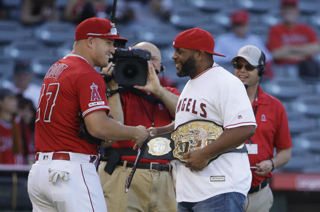 UFC heavyweight champion Daniel Cormier, right, shakes hands with Los Angeles Angels' Mike Trout after Cormier threw the ceremonial first pitch before the Angels' baseball game against the Pittsburgh Pirates on Wednesday, Aug. 14, 2019, in Anaheim, Calif. (AP Photo/Marcio Jose Sanchez)