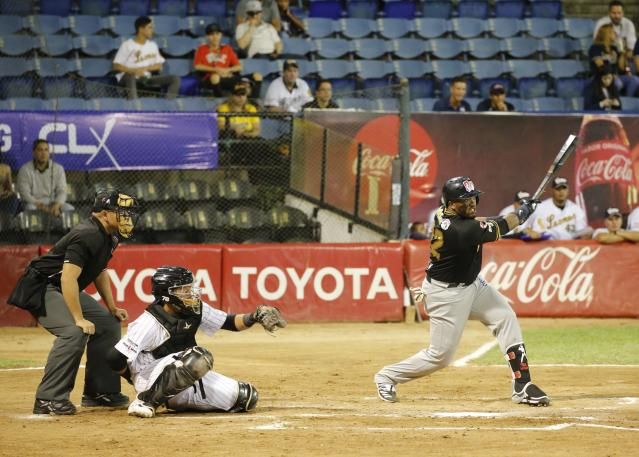 Tigres of Aragua player Yadir Drake, from Cuba, hits an single during the opening winter season game against Leones de Caracas in Caracas, Venezuela, Tuesday, Nov. 5, 2019. Drake said that when he and the other players step onto the diamond, politics is the last thing on their minds, especially when fans start shouting. (AP Photo/Ariana Cubillos)