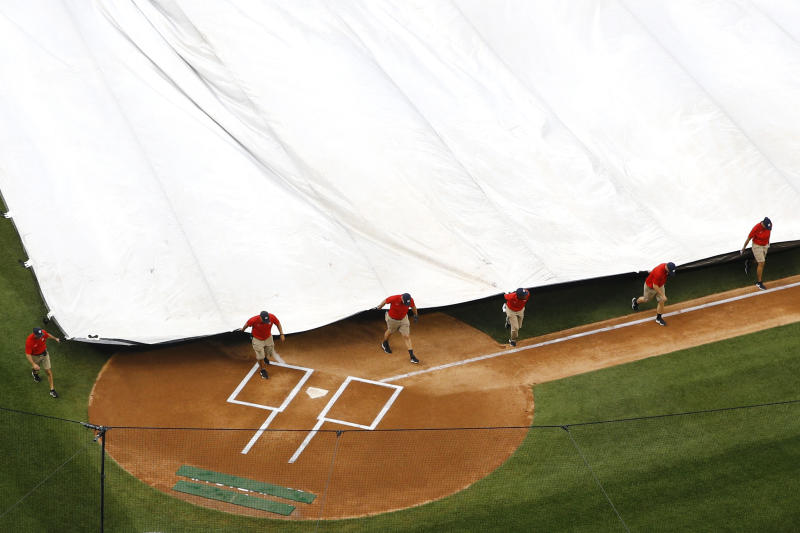 Grounds crew members pull a tarp over the infield during a rain delay before a baseball game between the Philadelphia Phillies and the Washington Nationals, Monday, June 17, 2019, in Washington. (AP Photo/Patrick Semansky)