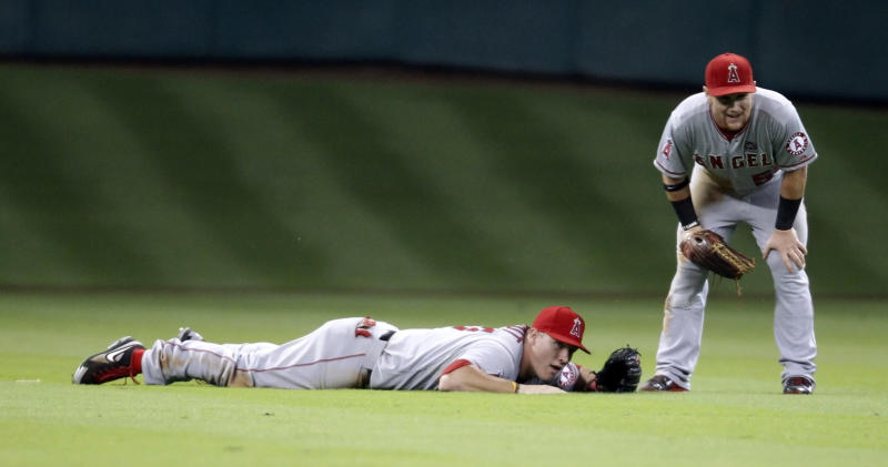Los Angeles Angels' Mike Trout, left, reacts to missing a shallow fly ball as Kole Calhoun stands next to him during the seventh inning of a baseball game against the Houston Astros Saturday, Sept. 14, 2013, in Houston. (AP Photo/Eric Christian Smith)
