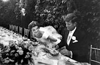 <p>Newlyweds John F. and Jacqueline Kennedy sitting down for a meal at their wedding reception. </p>