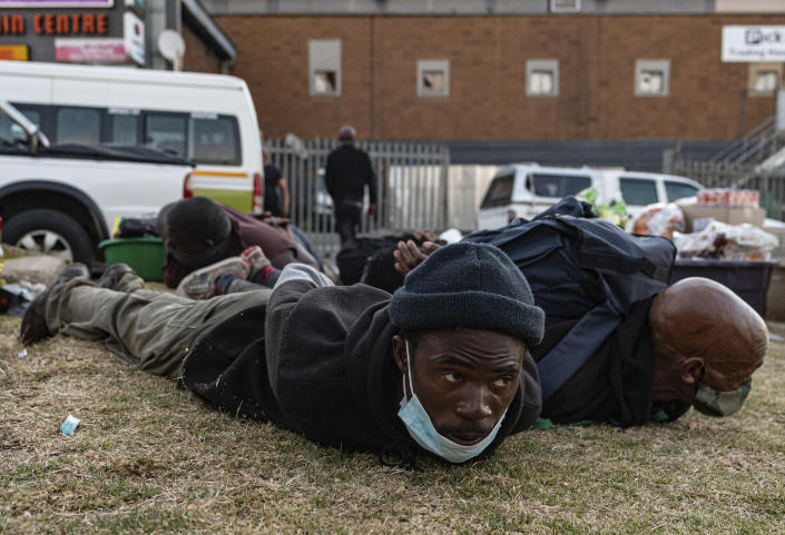 Suspect looters are held at the Bara taxi rank shops in Soweto, Johannesburg, Monday, July 12, 2021. Police say six people are dead and more than 200 have been arrested amid escalating violence during rioting that broke out following the imprisonment of South Africa's former President Jacob Zuma. (AP Photo/Ali Greeff)