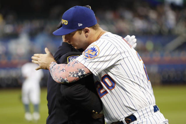 New York Mets' Pete Alonso embraces a member of the New York City Fire Department following a Sept. 11, 2001, tribute on the field before a baseball game between the Mets and the Arizona Diamondbacks, Wednesday, Sept. 11, 2019, in New York. (AP Photo/Kathy Willens)