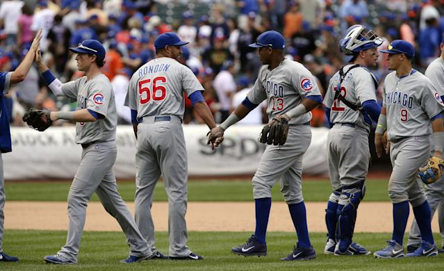 Chicago Cubs relief pitcher Hector Rondon (56) and shortstop Starlin Castro (13) celebrate after the ninth inning of a baseball game against the New York Mets at Citi Field, Sunday, Aug. 17, 2014, in New York. The Cubs won 2-1. (AP Photo/John Minchillo)