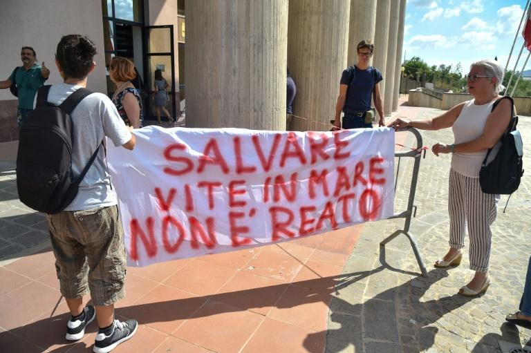 Rackete's supporters hold a banner reading 'Saving lives at sea is not a crime' outside the courthouse