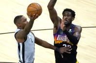 San Antonio Spurs guard Lonnie Walker IV (1) shoots next to Phoenix Suns center Deandre Ayton during the first half of an NBA basketball game Saturday, April 17, 2021, in Phoenix. (AP Photo/Rick Scuteri)