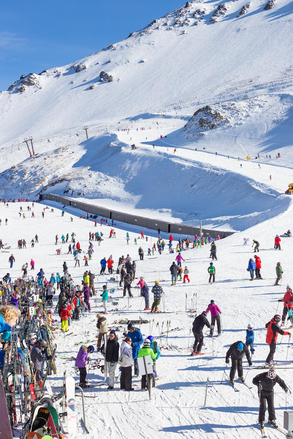 Mt Hutt, New Zealand August 10, 2014.  A very colorful crowd of skiers on a bright sunny winter's day on Mt Hutt in the South Island of New Zealand. Skiers are organizing themselves out on the ski slopes and getting ready to start skiing, with some skiers on the learners slope in the background.