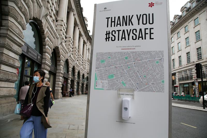 A woman wearing a face mask walks past a hand sanitizer station at Regents Street during coronavirus pandemic. It is mandatory to wear face masks while travelling. (Photo by Dinendra Haria / SOPA Images/Sipa USA)