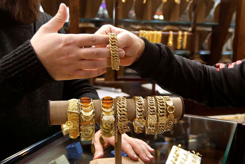 A salesman handles gold bracelet to a customer inside a jewellery shop in Beirut
