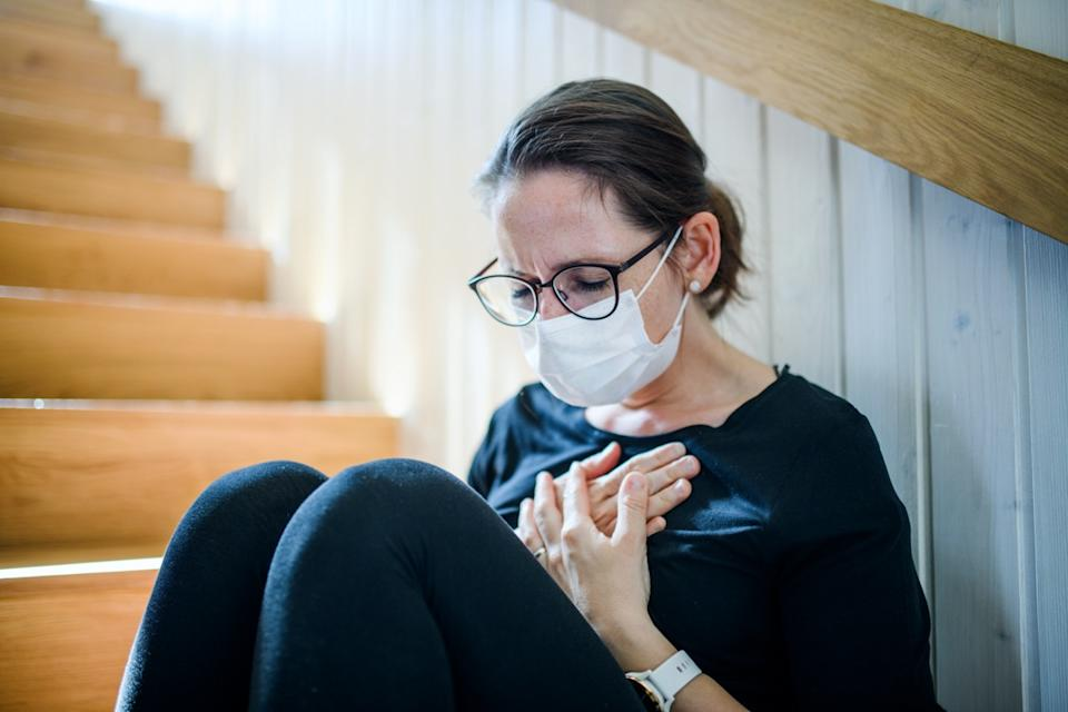 Woman with face mask and chest pain sitting indoors at home