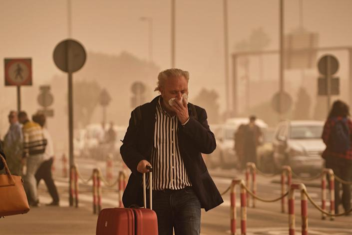 A passenger covers his nose and mouth in a cloud of red dust at the airport in Santa Cruz de Tenerife, Spain, Sunday, Feb. 23, 2020.