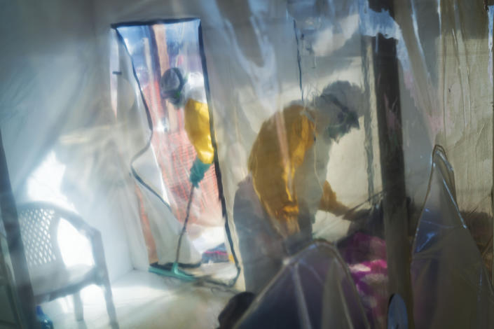 FILE - In this July 13, 2019 file photo, health workers wearing protective suits tend to an Ebola victim kept in an isolation cube in Beni, Congo. According to a report published in the New England Journal of Medicine on Wednesday, March 31, 2021, an African man who developed Ebola despite receiving a vaccine recovered, but he suffered a relapse nearly six months later that led to 91 new cases before he died. The report adds to evidence that the deadly virus can lurk in the body long after symptoms end, and that survivors need monitoring for their own welfare and to prevent spread. (AP Photo/Jerome Delay, File)
