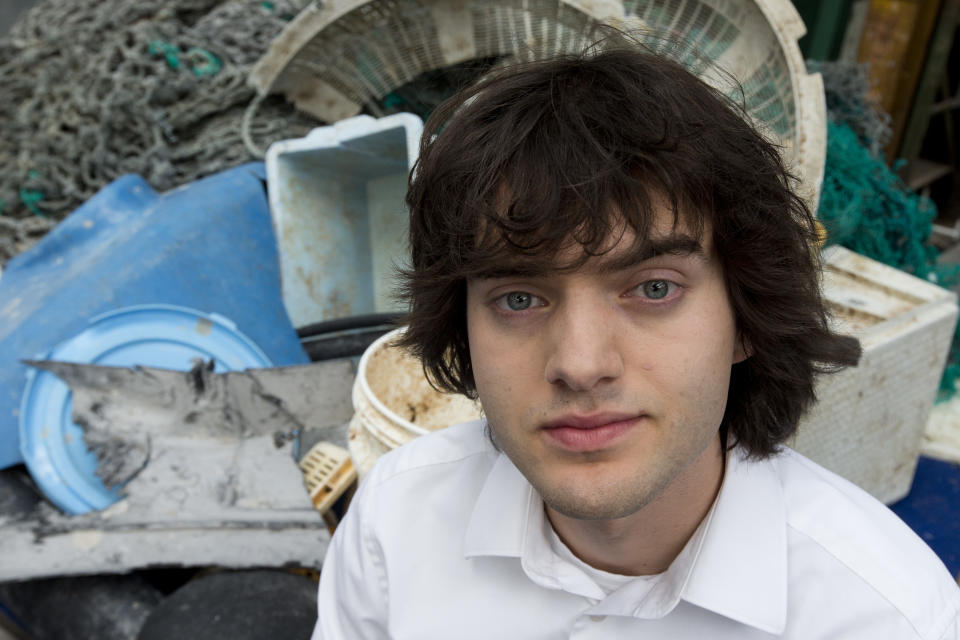 FILE - In this May 11, 2017, file photo, Dutch innovator Boyan Slat poses for a portrait next to a pile of plastic garbage prior to a press conference in Utrecht, Netherlands. A trash collection device deployed to corral plastic litter floating between California and Hawaii will be hauled back to dry land for repairs. Slat, who launched the Pacific Ocean cleanup project, tells NBC the 2,000-foot (600-meter) long floating boom will be towed to Hawaii. If it can't be repaired there it will be loaded on a barge and returned to its home port of Alameda, California. The boom broke apart under constant wind and waves. Slat says he's disappointed, but not discouraged. (AP Photo/Peter Dejong, File)