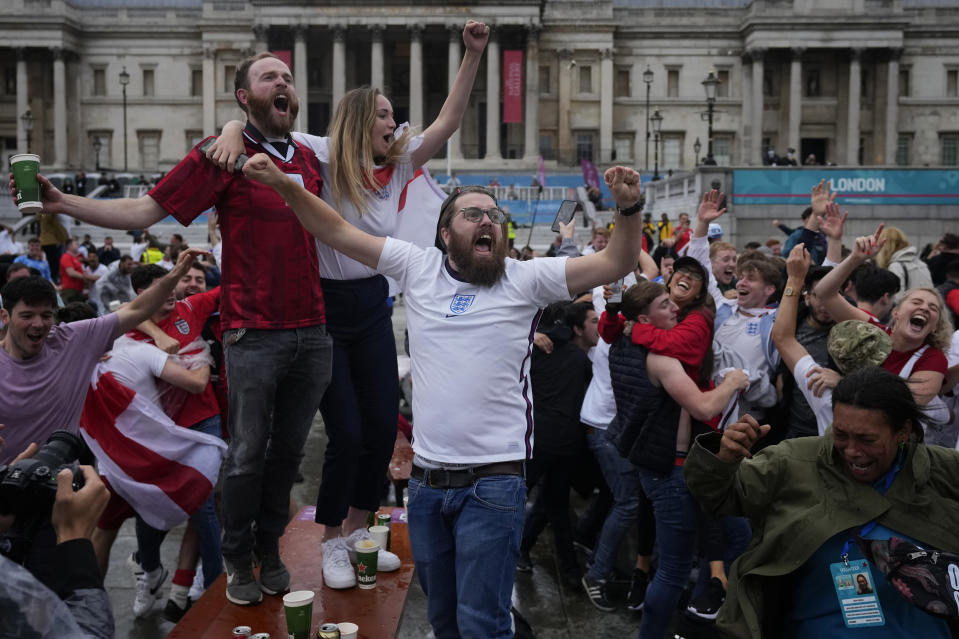 England fans celebrate at the end of the Euro 2020 round of 16 soccer championship match between England and Germany being played at London's Wembley stadium, at a fan zone in central Trafalgar Square in London, Tuesday, June 29, 2021. England won 2-0. (AP Photo/Matt Dunham)