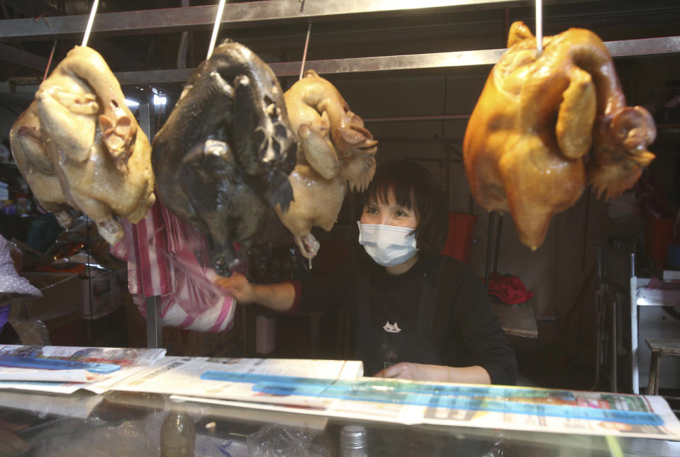 A vendor wears a face masks to help curb the spread of the coronavirus sells cooked chickens at a market in Taipei, Taiwan, Monday, Jan. 25, 2021. (AP Photo/Chiang Ying-ying)