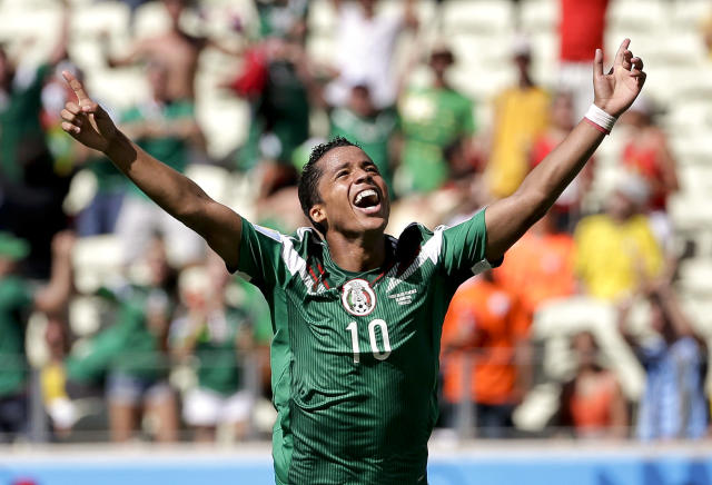 Mexico's Giovani dos Santos celebrates after scoring his side's first goal against Netherlands' goalkeeper Jasper Cillessen during the World Cup round of 16 soccer match between the Netherlands and Mexico at the Arena Castelao in Fortaleza, Brazil, Sunday, June 29, 2014. (AP Photo/Felipe Dana)