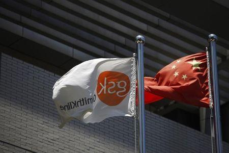 A flag bearing the logo of GlaxoSmithKline flutters next to a Chinese national flag outside a GlaxoSmithKline office building in Shanghai