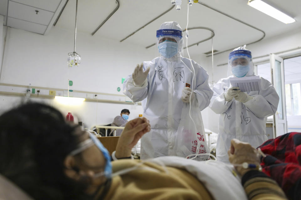 Medical workers check on the conditions of patients in Jinyintan Hospital, designated for critical COVID-19 patients, in Wuhan in central China's Hubei province Thursday, Feb. 13, 2020. China on Thursday reported 254 new deaths and a spike in virus cases of 15,152, after the hardest-hit province of Hubei applied a new classification system that broadens the scope of diagnoses for the outbreak, which has spread to more than 20 countries. (Chinatopix Via AP)