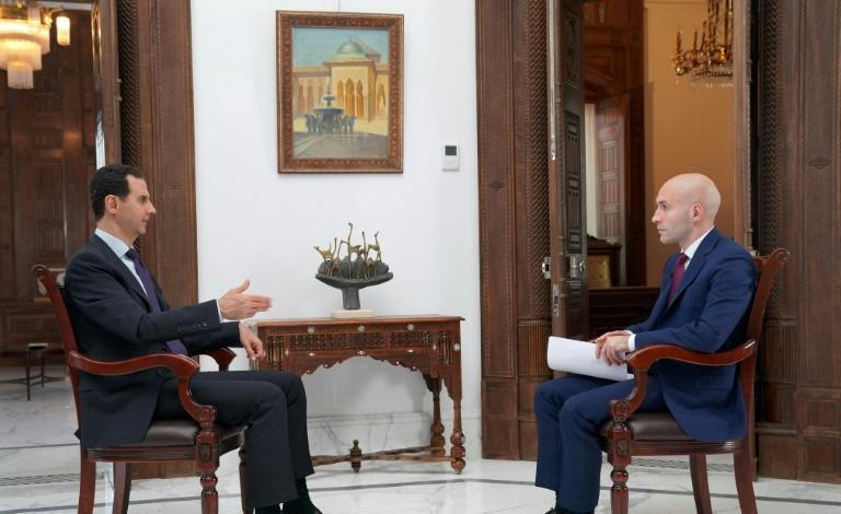 A handout picture released by the official Facebook page of the Syrian Presidency on May 31, 2018, shows Syrian President Bashar al-Assad (L) giving an interview to a journalist from Russia Today in the capital Damascus
