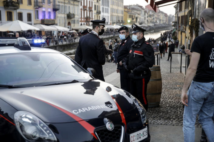 Carabinieri, Italian police officers, patrol the Naviglio Grande canal, in Milan, Italy, Saturday, Feb. 27, 2021. Police vans blocked entrance to Milan's trendy Navigli neighborhood Saturday evening after the mayor announced increased patrols to prevent gatherings during a spring-like weekend. The Lombardy region where Milan is located is heading toward a partial lockdown on Monday, and Mayor Giuseppe Sala said in a video message that he was disturbed by scenes of people gathering in public places, often with their masks down. (AP Photo/Luca Bruno)