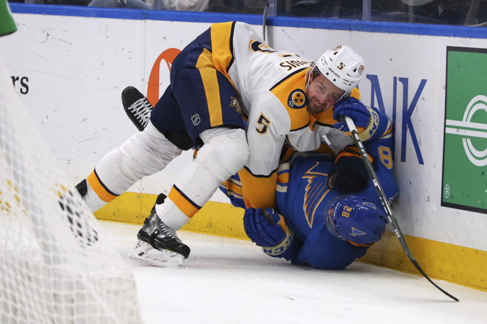 Nashville Predators' Dan Hamhuis (5) pins St. Louis Blues' Mackenzie MacEachern (28) to the ice during the second period of an NHL hockey game Saturday, Nov. 23, 2019, in St. Louis. (AP Photo/Dilip Vishwanat)