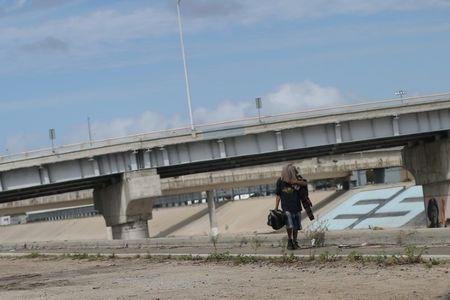 A Mexican who was recently deported from the U.S. walks by the Tijuana river, in Tijuana