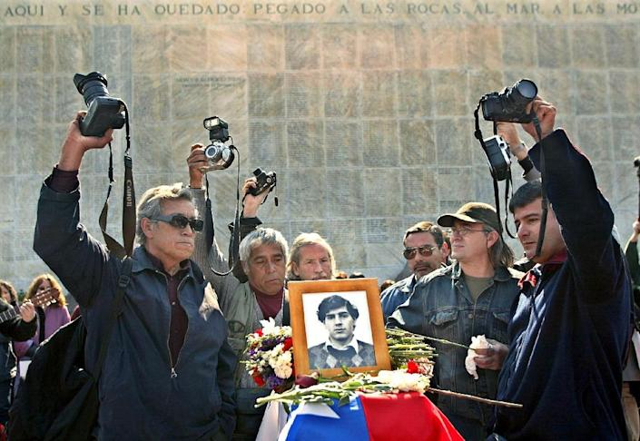 A group of photographers, colleagues of Rodrigo Rojas, raise their cameras at the Memorial of the Detained and Disappeared in Santiago, on August 23, 2003 (AFP Photo/Victor Rojas)