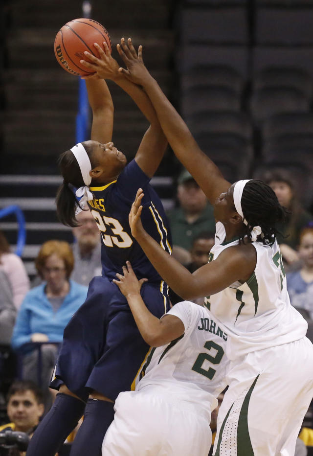 West Virginia guard Bria Holmes (23) shoots over Baylor guard Niya Johnson (2) and point Sune Agbuke (22) in the first half of an NCAA college basketball game in the finals of the Big 12 Conference women's college tournament in Oklahoma City, Monday, March 10, 2014. (AP Photo/Sue Ogrocki)