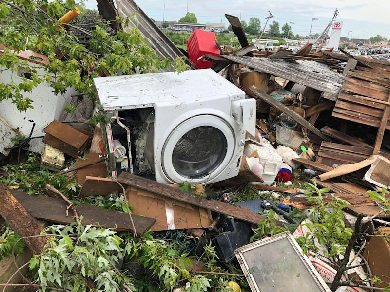 Debris from a home that David Surprenant rents with his family is scattered across the lawn Thursday, May 23, 2019, the morning after a tornado hit Jefferson City, Mo. Surprenant said his family fled to the basement while he watched the sky outside. Officials are going door-to-door to survey damage after a tornado ripped a 3-mile path through Missouri's capital city. The destruction in Jefferson City was part of an outbreak of severe weather overnight. (AP Photo/Summer Ballentine)