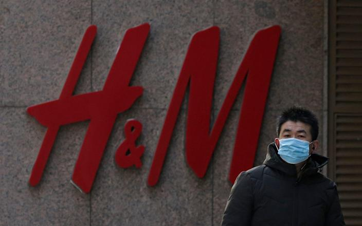 A man wearing a face mask walks by a Swedish fashion brand H&M store outlet in Beijing - AP