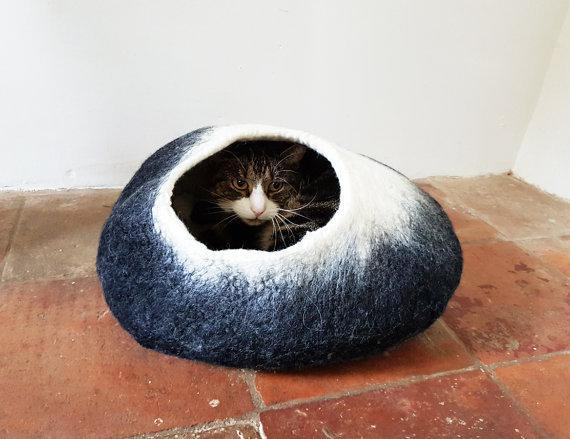 """<p>This hand made felted wool cat bed is the perfect hideaway for your furry friend. Comes with the option of personalising it with your cat's name.</p><p>£32 <a href=""""https://www.etsy.com/uk/listing/476357176/black-and-white-cat-bed-cat-cave-cat?ref=shop_home_active_1"""" rel=""""nofollow noopener"""" target=""""_blank"""" data-ylk=""""slk:Love Cat Caves"""" class=""""link rapid-noclick-resp"""">Love Cat Caves</a></p>"""